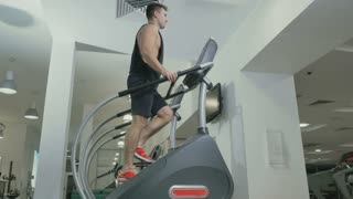 Guy training legs moving up stairs in the gym