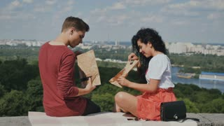 Guy with girl are eating pizza at city background
