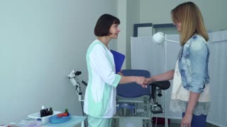 Gynecologist greeting young woman and invite her to gynecological chair