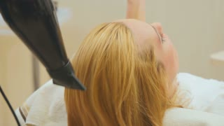 Hairdresser dries wet hair of blonde with hairbrush
