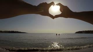 Hand heart against the sun