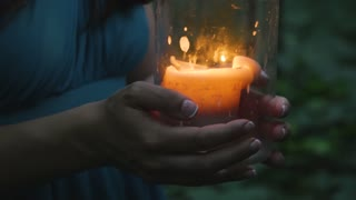 Hands of the girls hold a burning candle in the forest in the evening