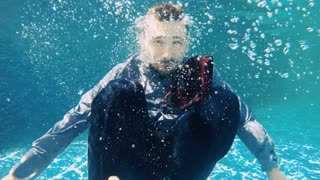 Handsome businessman swims under water in suit