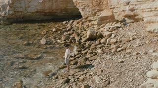 Handsome guy enjoys the sea on the rocky coast