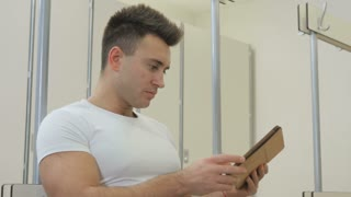 Handsome guy uses tablet in dressing room