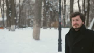 Handsome man coughs in the snowy park