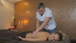 Handsome man massaging the girl's back in the spa