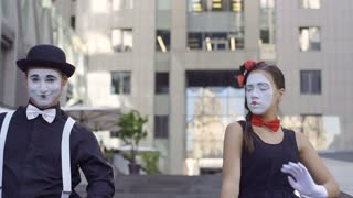 Handsome man mime give invisible flower to his girlfriend
