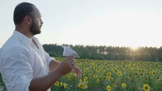 Handsome man throws paper airplane to the sunset in sunflowers field