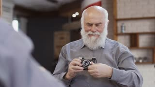 Handsome mature man makes selfie with an old camera in the mirror