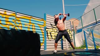 Handsome muscular man training with hammer on the outdoor ground