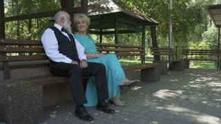 Handsome old man and pretty old woman resting on bench in park