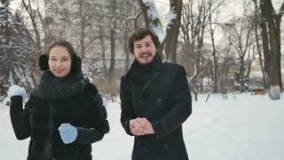 Handsome people throw the snowballs in the winter park