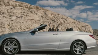 Happy blonde with man driving in the cabriolet