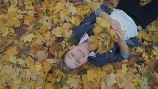 Happy boy lays on autumn leaves