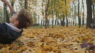 Happy boy lays on yellow leaves in autumn park