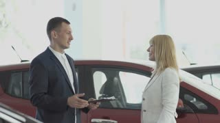 Happy businesswoman gets a car keys from salesman in car dealership