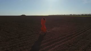 Happy carefree girl in red dress running through plowed field