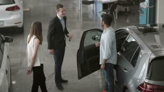 Happy couple bought a modern car in car showroom
