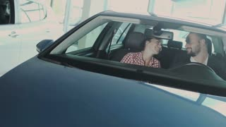 Happy couple kisses and enjoys a new automobile in the car dealership