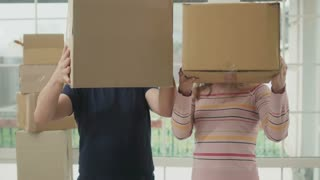 Happy couple peers out from boxes