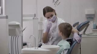 Happy dentist and little patient shows thumb up
