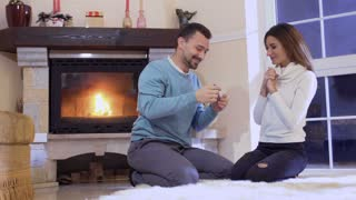 Happy family celebrates a wife pregnancy near fireplace