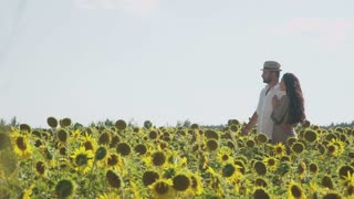 Happy family embraces at the sunflowers field