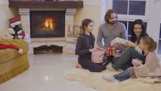 Happy family exchanges christmas gifts near fireplace