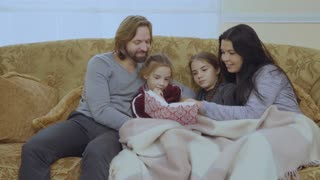 Happy family reads fairytale together on the sofa