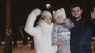 Happy family waves hands at the evening winter park