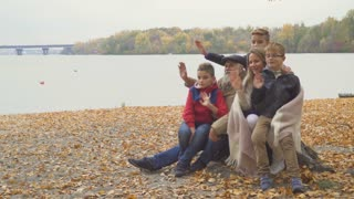 Happy family waves hands in autumn park