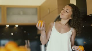 happy girl fooling with oranges on kitchen