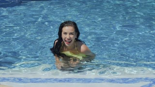 Happy girl with red lips dances in the swimming pool