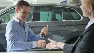 Happy guy gets a car's keys in automobile salon