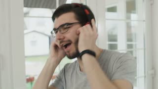 Happy guy listens music in headphones in slowmotion
