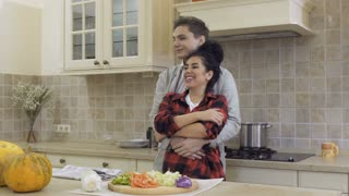 Happy in love couple hugs at the kitchen
