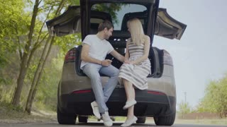Happy in love couple sit inside th trunk of the car and talking, first date