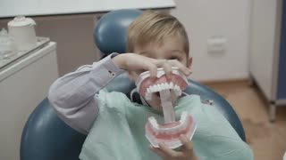 Happy little boy plays with plastic form of human jaw in dentist chair