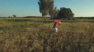 Happy little girl walks with red umbrella on the meadow