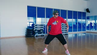 Happy man in cap and sunglasses dancing in the gym