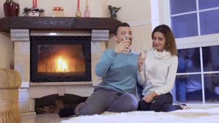Happy married couple with champagne near fireplace