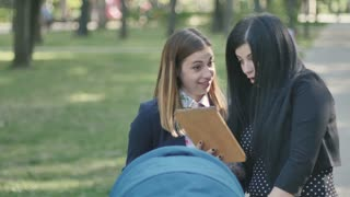 Happy mom and pretty brunette use the tablet in a park