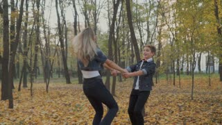 Happy mother and son turns around in autumn forest