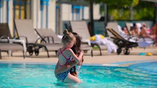 Happy mother have a good time with her daughter in the swimming pool