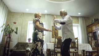 Happy senior couple dancing at home
