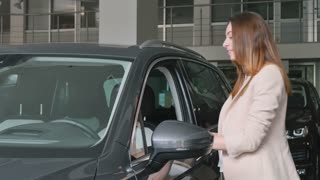 Happy woman buys a car in the showroom