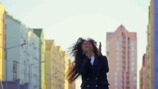 Happy woman jumps at the street in slowmotion