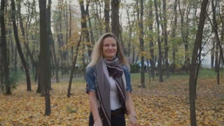 Happy woman walks in autumn park with bouquet of leaves