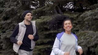 Happy young couple runs in the forest